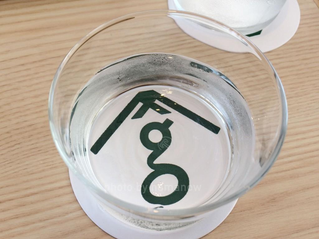 サングラムのロゴが入ったコースターと水