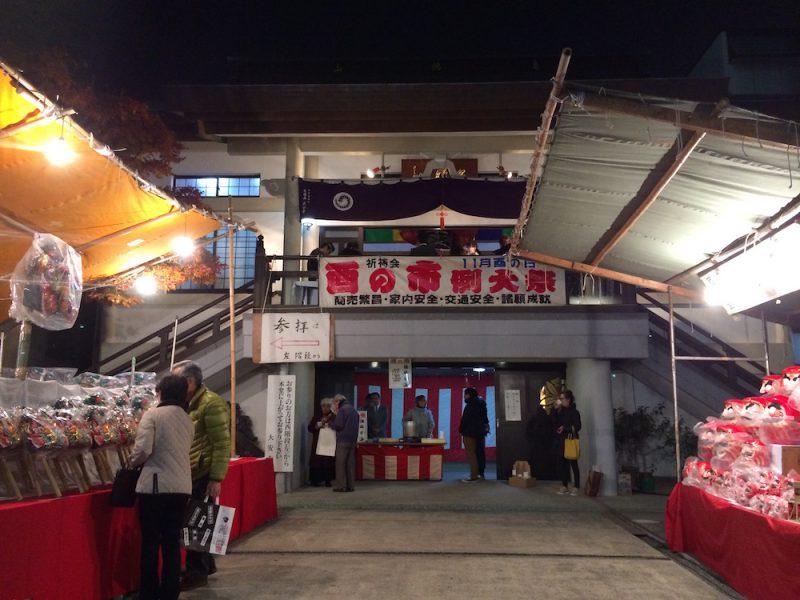大安寺で熊手を買い求める人