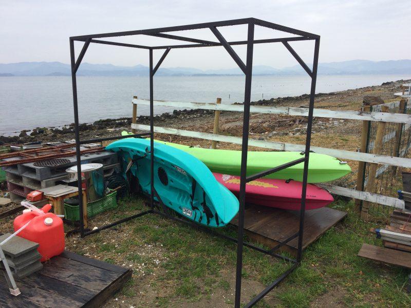 青、緑、赤の3艘のカヌーが置いてある
